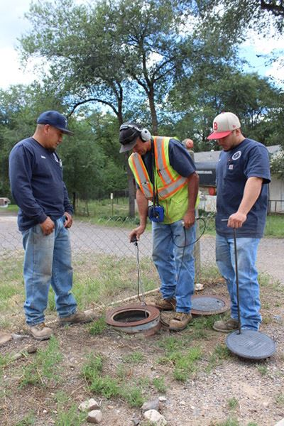 Manny Orosco, Silver City utilities foreman, Chris Haley and Johnny Baca, both water crewman, check a local water meter for leaks, using sonic-wave technology leak detection equipment
